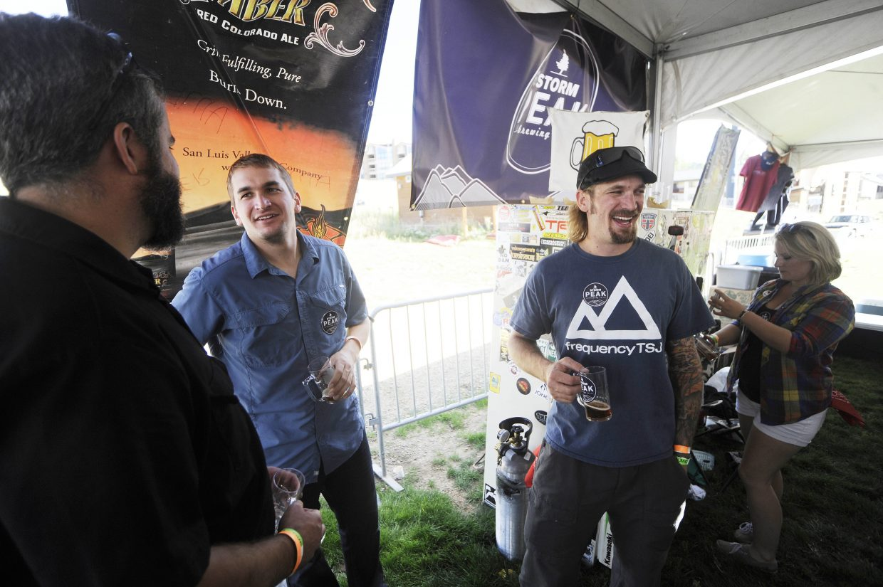 Storm Peak Brewing Co. brewers Wyatt Patterson, right, and brother Tyler Patterson, middle, visit with Butcherknife Brewing Co. brewer Mark Fitzgerald on Saturday during OktoberWest.