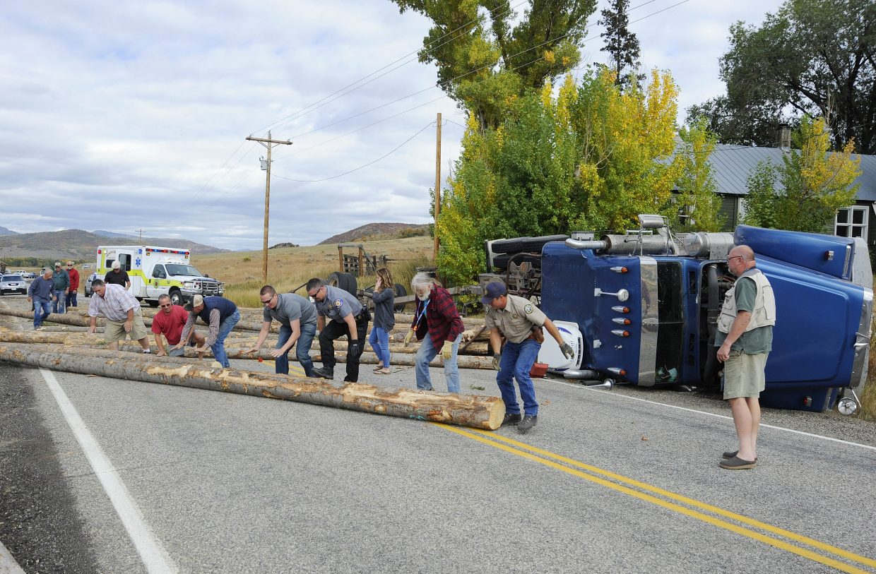 Emergency responders and bystanders remove logs from Routt County Road 129 after a truck crashed Wednesday morning.