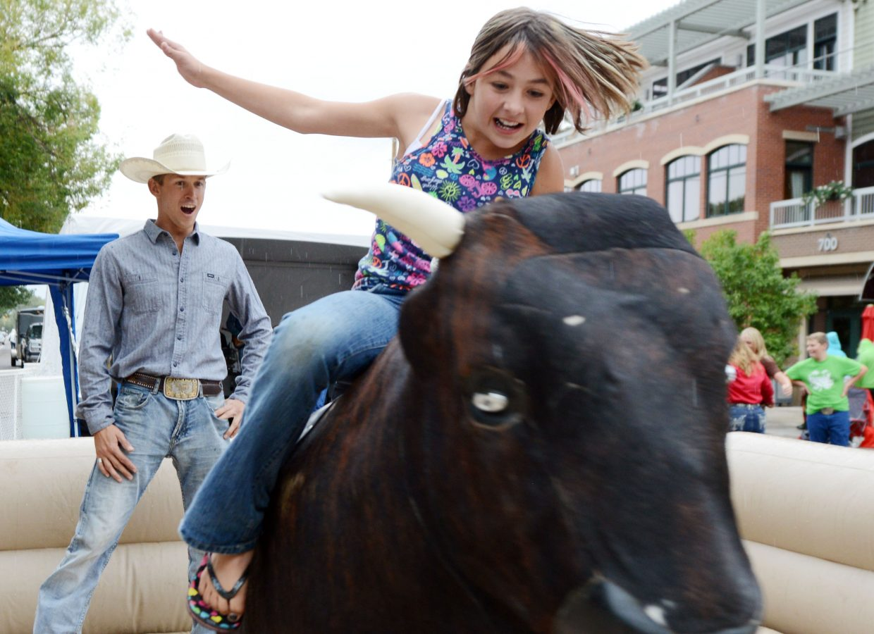 Haven Arcurio, 11, hangs on tight to a mechanical bull on Sunday at the Yampa Live event in downtown Steamboat Springs. Several riders took turns trying to best the bull even as it began to sprinkle Sunday afternoon, but Arcurio proved to have a knack for it, showing up many bigger, stronger foes.