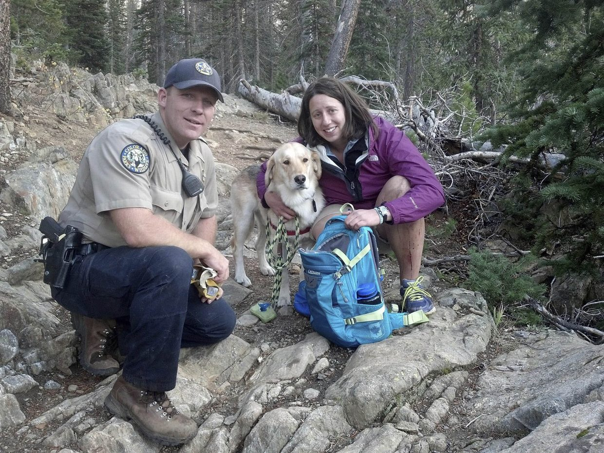 Colorado Parks and Wildlife ranger Robert Seel is pictured with an unidentified Denver woman, whose dog slipped down a steep ravine Tuesday.