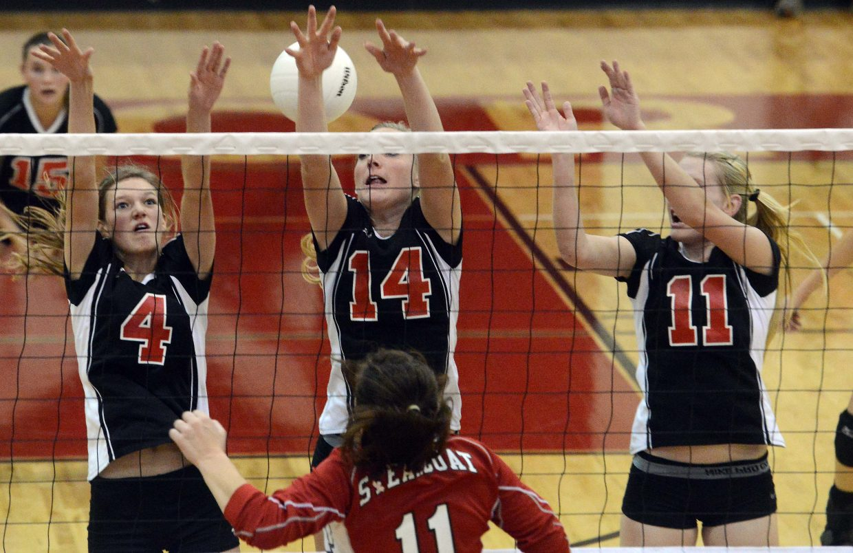 Maddie Robertson falls back after driving a ball between a trio of Eagle Valley blockers. Steamboat was at its best the longest in a streaky match Tuesday against the Devils, winning in four sets.