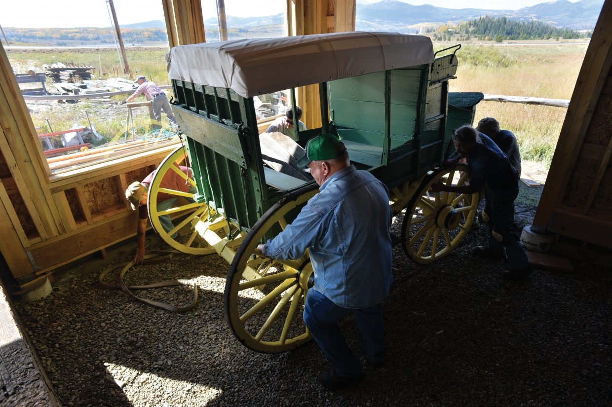 Volunteers move a historic stagecoach into a new addition to the pole barn in Hahn's Peak Wednesday afternoon. The Lowell Whiteman School, now Steamboat Mountain School, donated the stage, which ran the final leg of the Wolcott to Hahn's Peak Line, to the Hahn's Peak Area Historical Society. The stage was refurbished, and will be on display for special occasions this winter and when the pole barn opens to visitors next summer.
