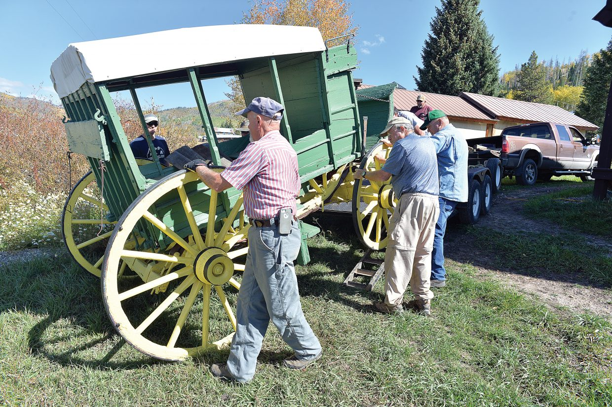 Volunteers move a historic stagecoach off a flatbed trailer to a new addition to the pole barn in Hahn's Peak on Wednesday afternoon. The Lowell Whiteman School, now Steamboat Mountain School, donated the stage, which ran the final leg of the Wolcott to Hahn's Peak Line, to the Hahn's Peak Area Historical Society. The stage was refurbished, and will be on display for special occasions this winter and when the pole barn opens to visitors next summer.