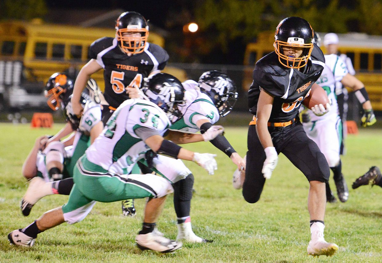 Hayden's Jack Redmond tries to outrun a pair of Rangely defenders Friday. He made it on that play, but the Panthers had just enough to beat the Tigers at home, winning in overtime, 20-14.