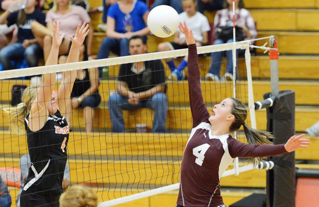 Soroco's Laramie Parker tips the ball over in front of Hayden's Jordan Temple on Friday. Every game was bitterly close, but Soroco won in the end, knocking off the Tigers in four sets.
