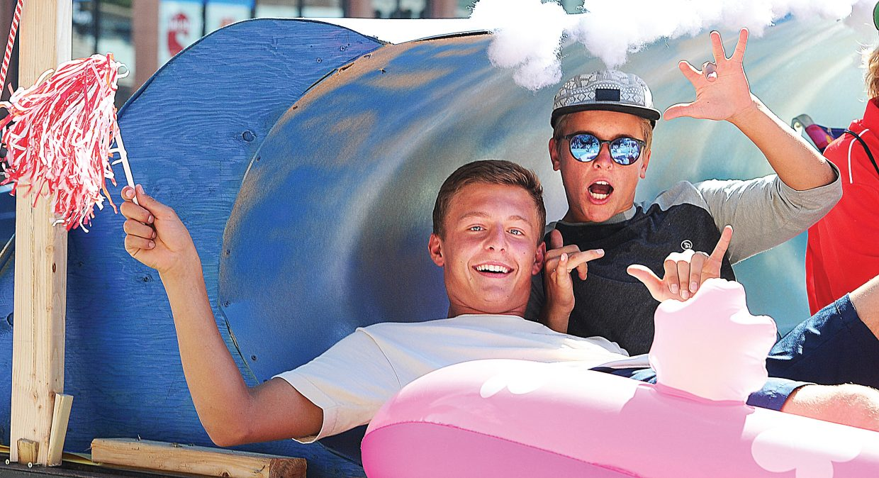 Steamboat Springs High School students Nick Simon, left, and Matthew White enjoy riding a wave and a float in the 2014 Homecoming Parade, which took place Friday afternoon on Lincoln Avenue.
