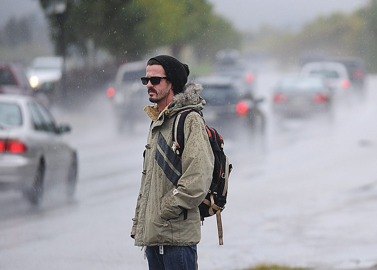Justin McClumg waits for a bus in the rain and snow Friday afternoon in Steamboat Springs.