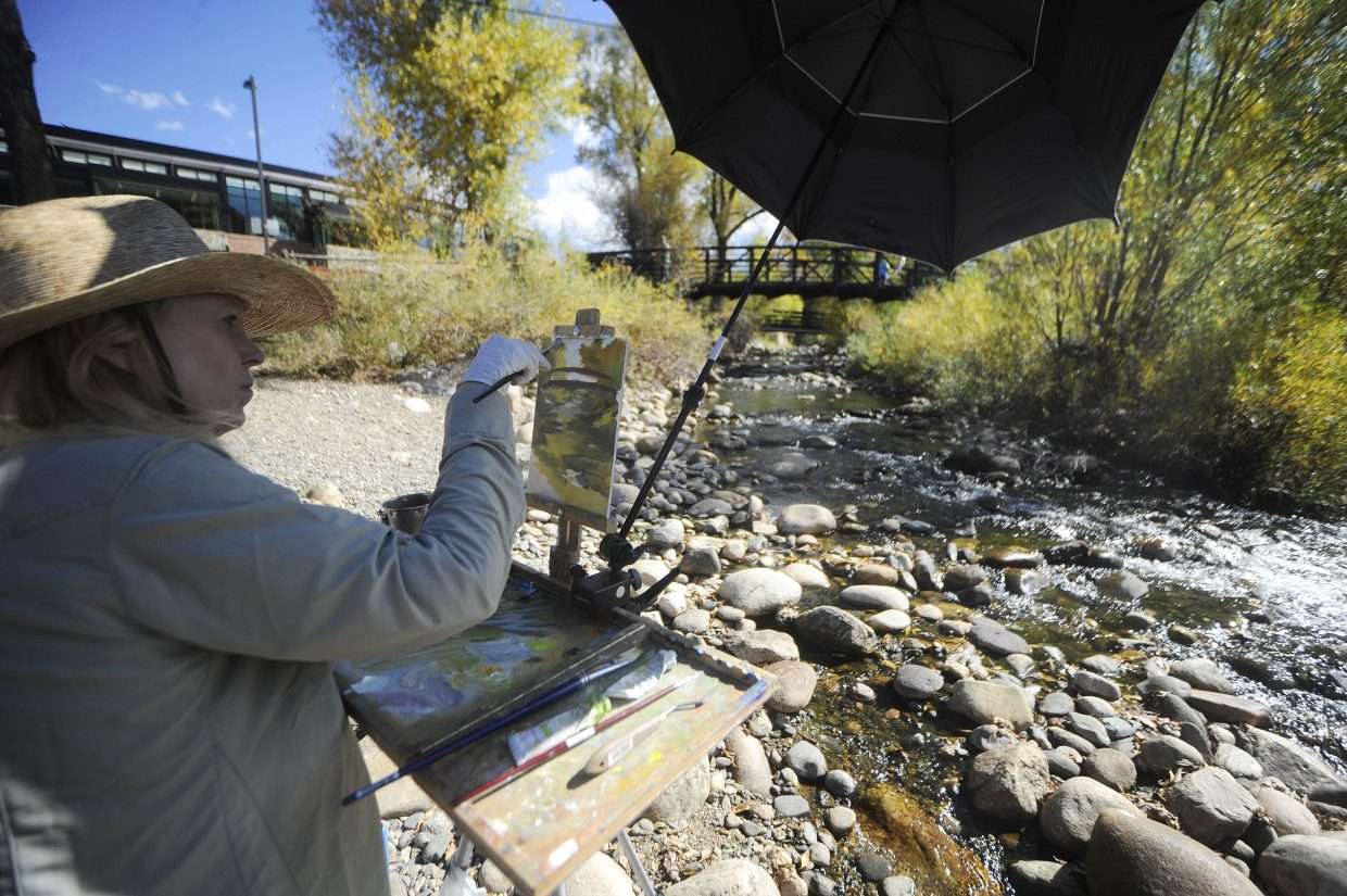 Larkspur resident Karin Toppel works on her painting along the Yampa River on Saturday during the Steamboat Art Museum's plein air painting Quick Draw event.