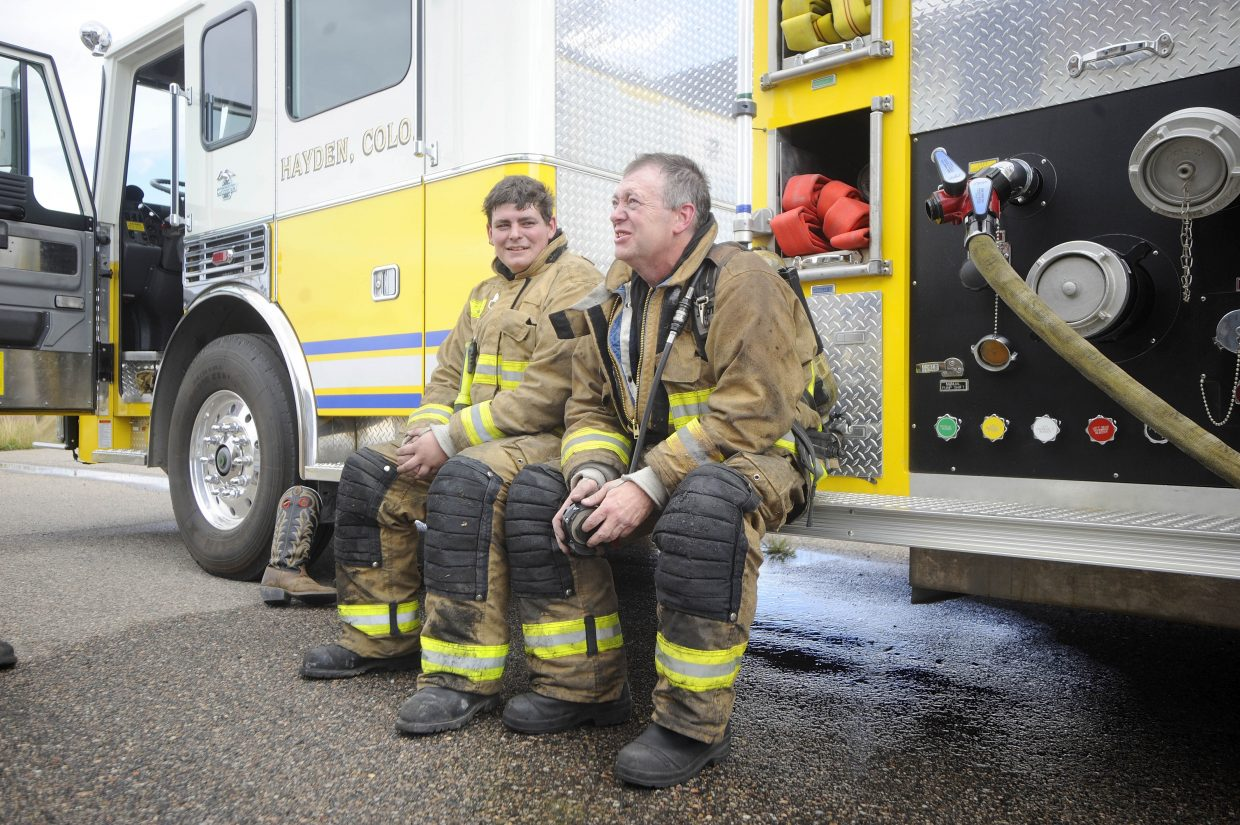 Wayne DeLuca, right, sits with his son Nick after training Sept. 7 at the Hayden fire training facility. The Hayden department has four sets of father-son firefighters.