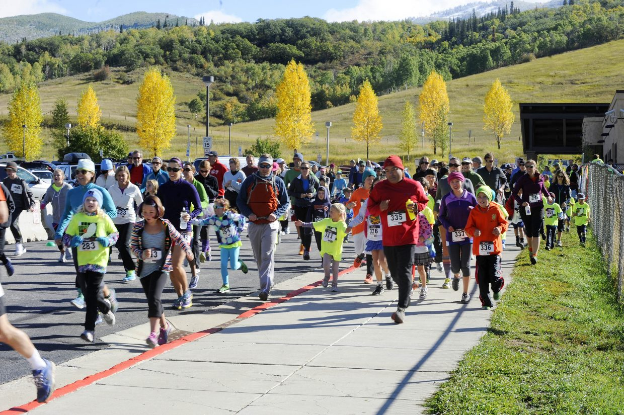 Children and parents start the Steamboat Sneak 5-kilometer running event Saturday at Steamboat Springs Middle School.