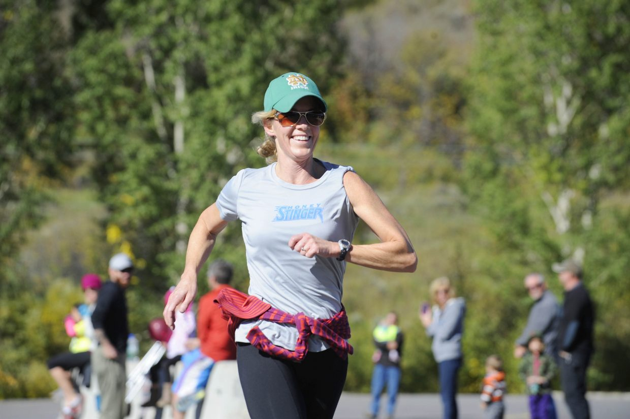 Strawberry Park Elementary School fourth-grade teacher Lisa Adams approaches the finish line during the Steamboat Sneak 5-kilometer running event Saturday at Steamboat Springs Middle School.