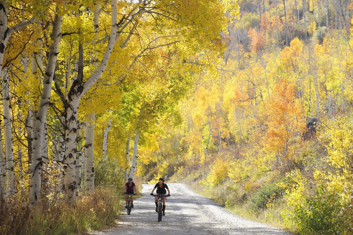 Steamboat Springs residents Alex Masse, left, and Mindy Mulliken ride under the changing aspen trees Wednesday evening on Buffalo Pass.