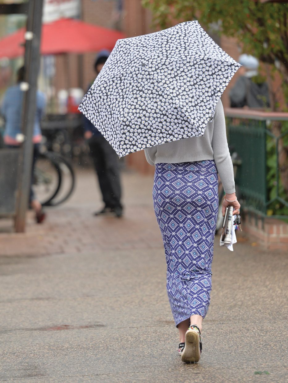 Zoe Hart strolls downtown during Monday afternoon's rain showers. Hart's flower-covered umbrella seemed to help put the autumn weather in perspective.
