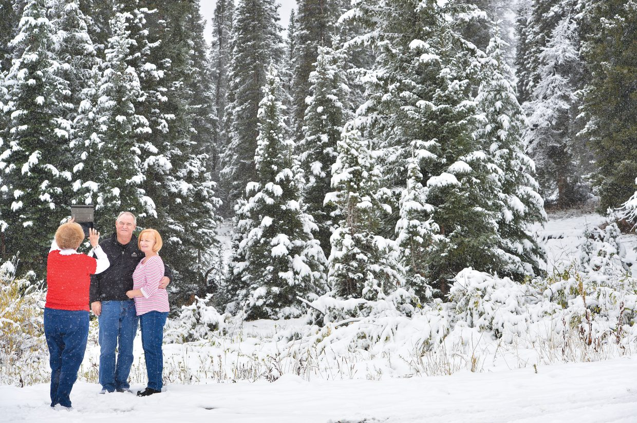 Pat Hawkins takes Julian, left, and Patty Wells' photograph Wednesday afternoon at the top of Rabbit Ears Pass. The group, from Alabama and North Carolina, wanted to stop along U.S. Highway 40 and have a photograph taken in the snow.