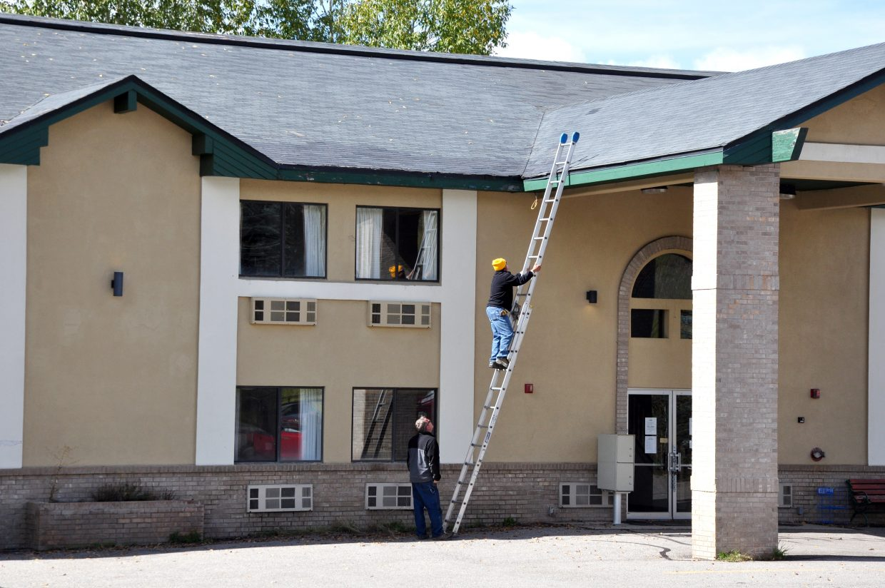 Joe Dickerson climbs to the top of the Iron Horse Inn on Thursday to take measurements in preparation for a possible roof repair. The city is working to finalize an agreement with the Sheraton Steamboat Resort to rent the property to Sheraton employees this winter.