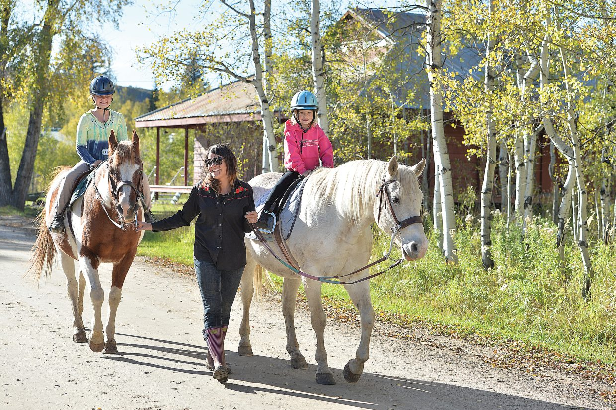Riding instructor Tessa Hill leads 10-year-old Paige Watson, left, and her 6-year-old sister Emmy along the road at the Perry-Mansfield Performing Arts School and Camp to the riding arena. It was the girls first riding lesson.