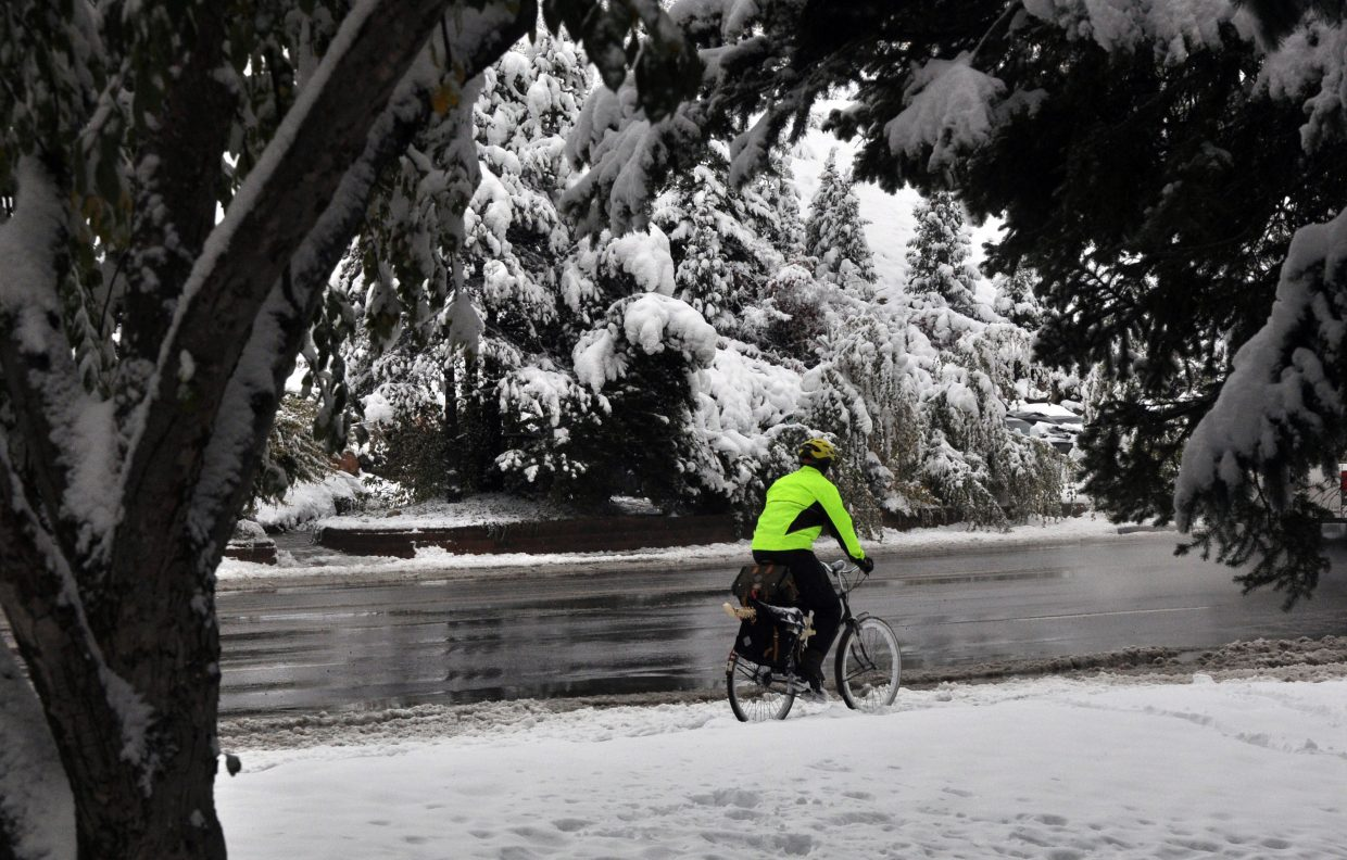 A man bikes on a snowy sidewalk near the Old Town Hot Springs on Friday morning. The city received more than 10 inches of snow overnight.