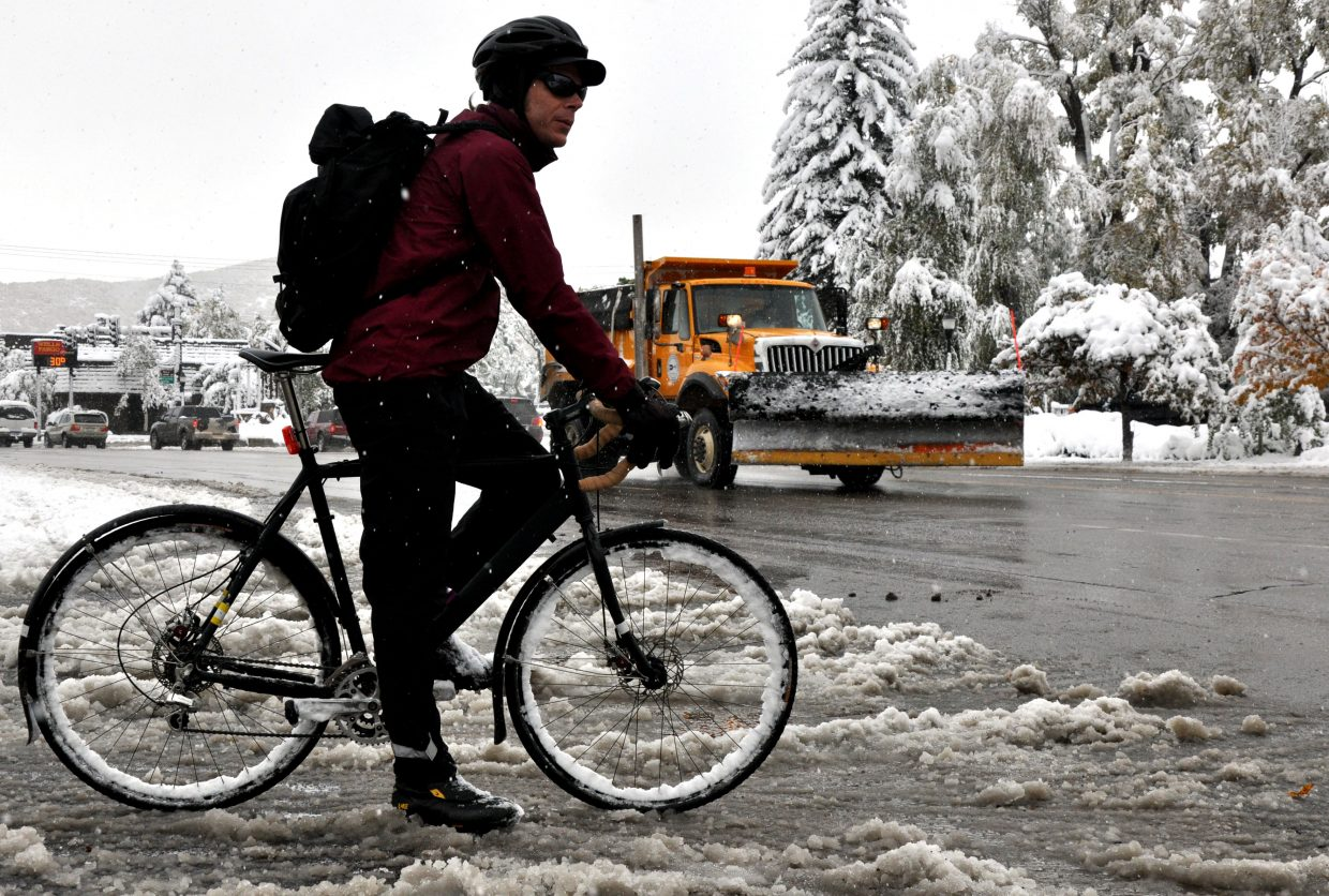 Doug Demusz waits to bike across Lincoln Avenue on Friday morning to get to the Old Town Hot Springs. The city received more than 10 inches of snow overnight.