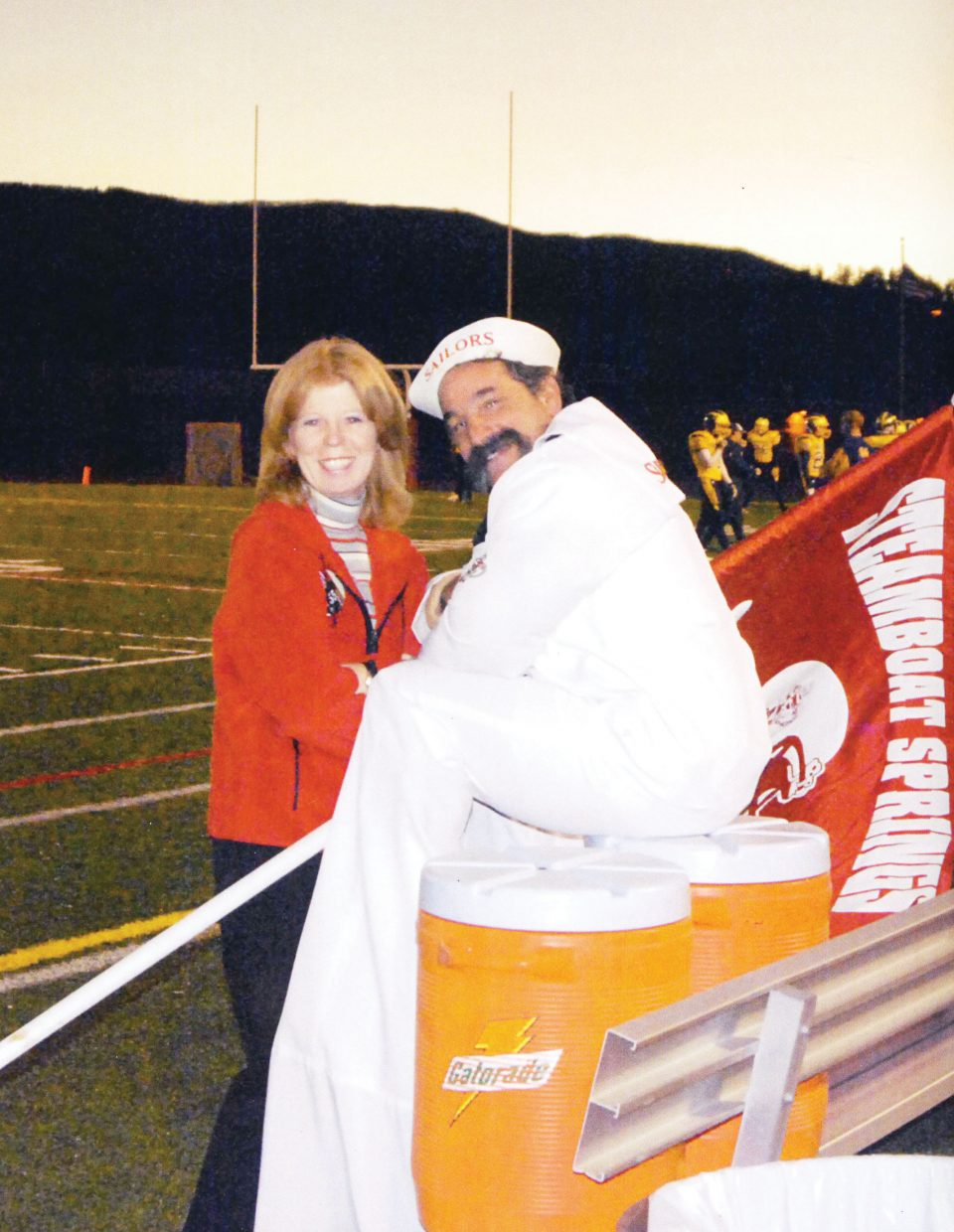 Kevin, dressed as Salty the Sailor, and Kathy Nerney pose for a photo at a Sailors football game.