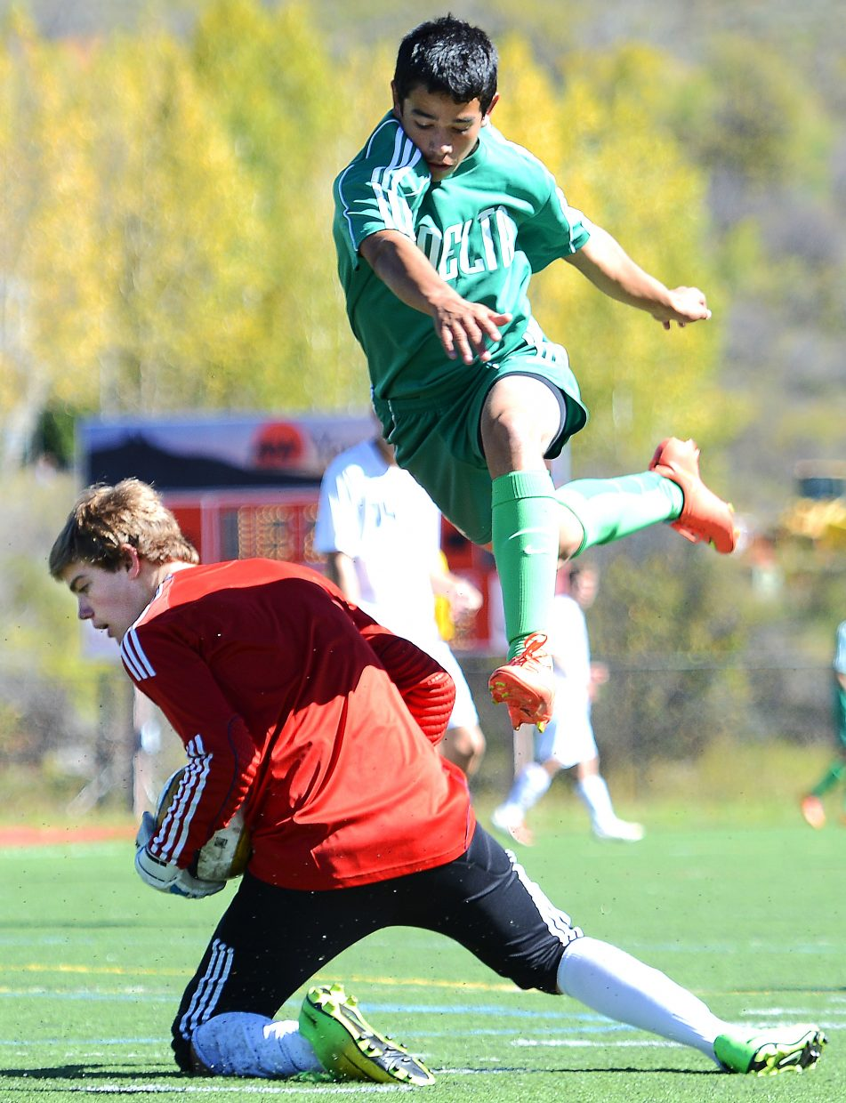 Steamboat goalie Andrew McCawley, who came in for the second half Saturday, ducks with the ball as a Delta player flies high over his back.