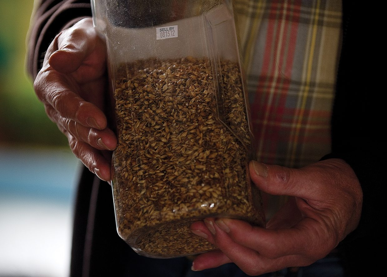 Ken Proper holds a container of grain the he uses to make his own specialty beers.