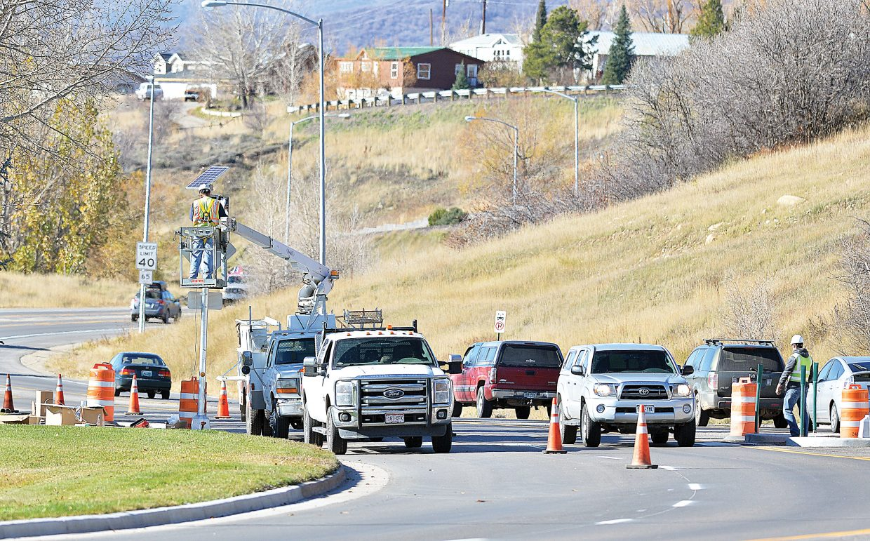 Crews install signs and lights at a new pedestrian crossing on the west side of downtown Steamboat Springs on Tuesday afternoon. The crossing is designed to help pedestrians cross safely from one side of Lincoln Avenue to the other for bus service.