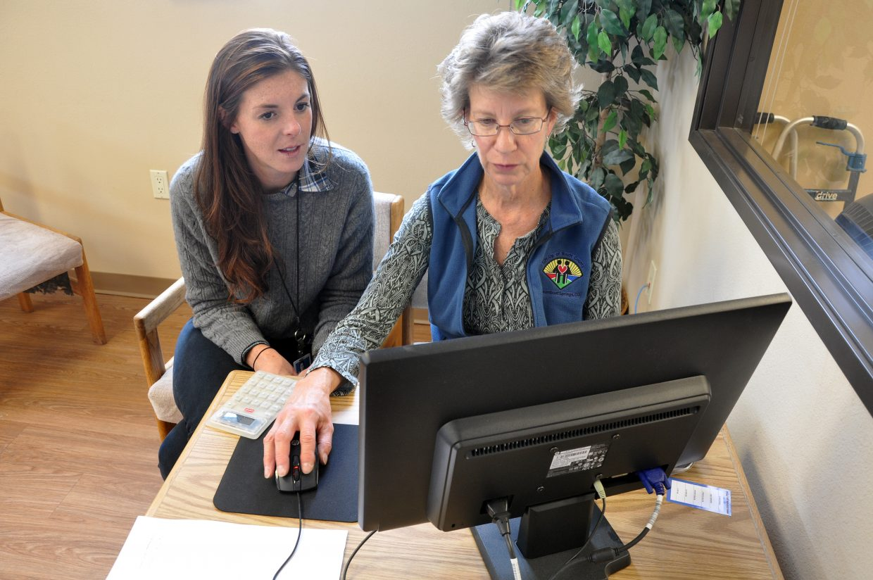 Erin Gleason, left, helps LIFT-UP of Routt County Assistant Thrift Store Manager Nancy Mayer shop for a new health insurance plan Friday. The launch of Colorado's new health insurance exchange will allow some people to get more affordable health insurance.