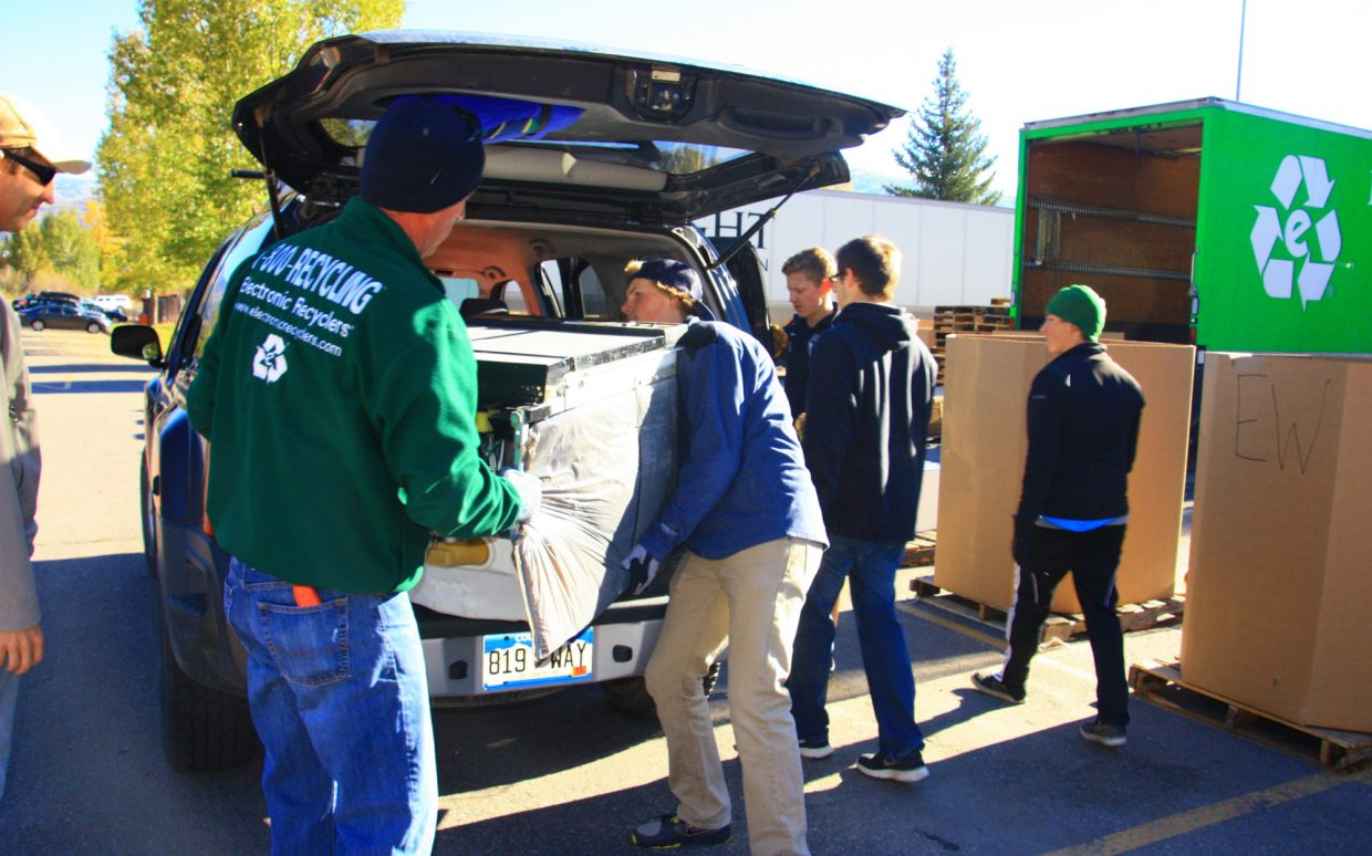 Joe Haight, center, and Charlie Robinson, left, unload items to be recycled Saturday at the fifth annual Community Recycling Drop-Off Day in Steamboat Springs.