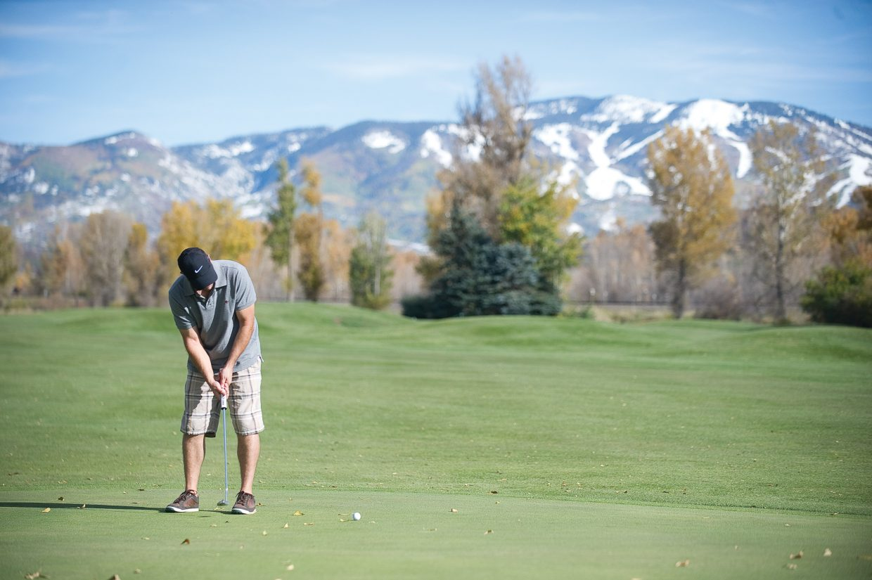 Golfer Kyle Re hits his putt on the No. 9 hole at the Steamboat Golf Club on Monday afternoon. Last week's storms closed the course for a couple of days, but business has been good since it reopened Sunday. The nine-hole course plans to remain open until Nov. 3, weather permitting. Haymaker also will reopen the entire course and Rollingstone Ranch Golf Club plans to reopen its front nine by Wednesday.