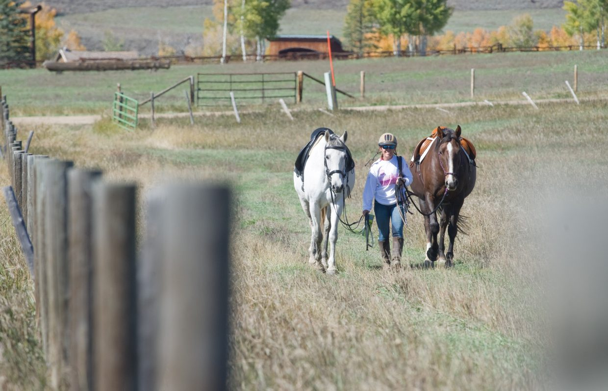 Claudia Dausman walks her horses to a riding arena along Routt County Road 129 on Monday. The snow and cold weather seemed to be a distant memory Monday afternoon as temperatures seemed more like summer.