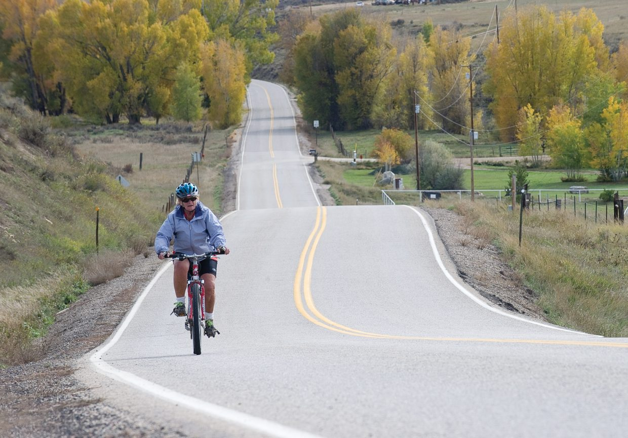 Carla Portigal takes advantage of a warm fall day to ride her bike along Routt County Road 33 just outside Steamboat Springs.