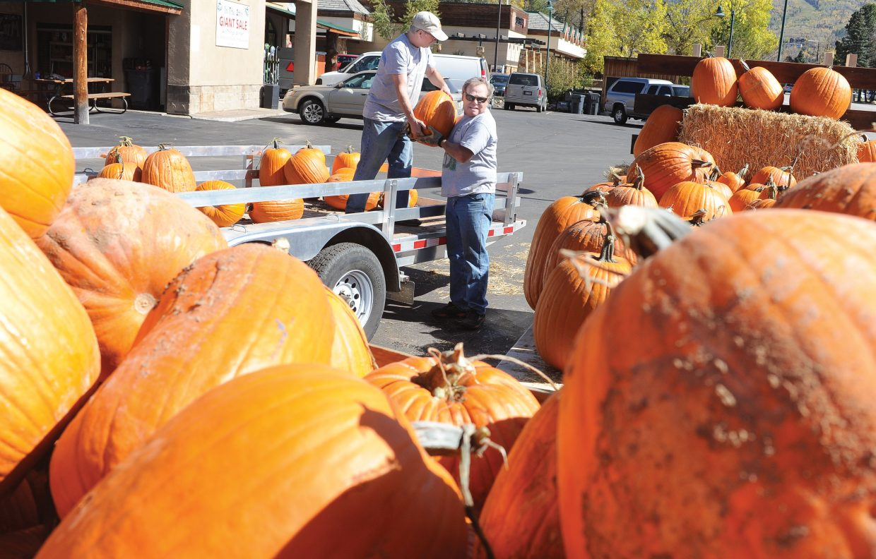 Ski Haus owner Rob Schrage and Bill Paul unload pumpkins outside the Steamboat Springs store. Each year, Schrage buys the pumpkins from the same family in Delta and brings them to Steamboat Springs, where they are on display in the bed of his vintage Diamond T pickup.