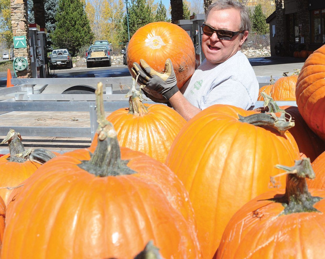 Ski Haus owner Rob Schrage unloads pumpkins outside the Steamboat Springs store. Each year, Schrage buys the pumpkins from the same family in Delta and brings them to Steamboat Springs, where they are on display in the bed of his vintage Diamond T.