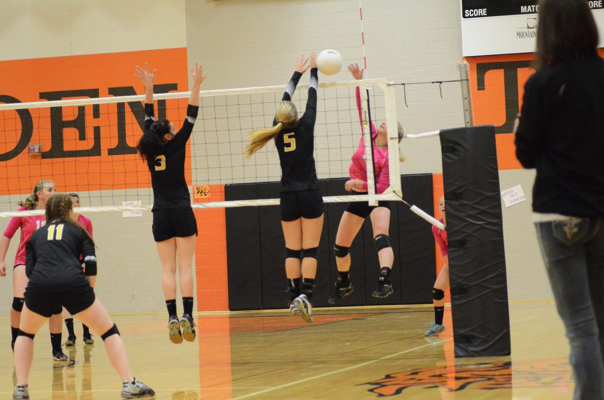 Hayden High School sophomore Allison Ingols, far right, goes up against two Meeker defenders during the Tigers' Saturday match with the Meeker Cowboys. The Cowboys won the match in four sets.