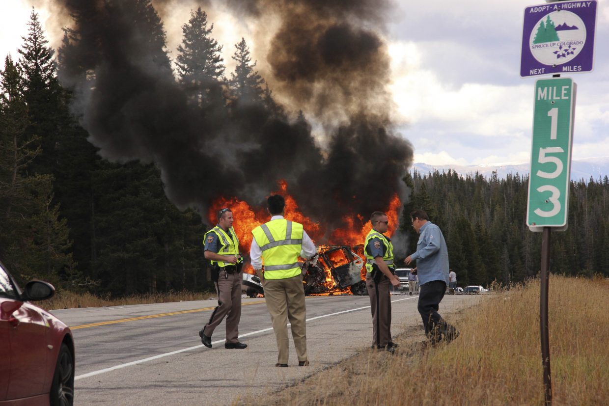 The driver of a semi involved in a fatal accident Friday on Rabbit Ears Pass talks to a trooper while the sport-utility vehicle involved in the accident burns. The woman inside the car died.