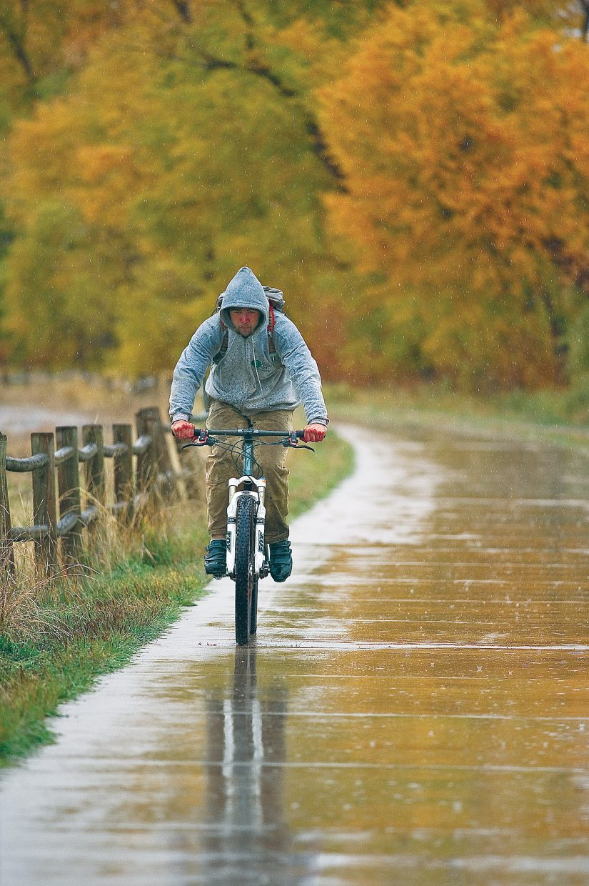 Doug Cummings heads home in the rain Thursday afternoon in Steamboat Springs. The area is expected to receive snow and rain through Friday evening, according to the National Weather Service.