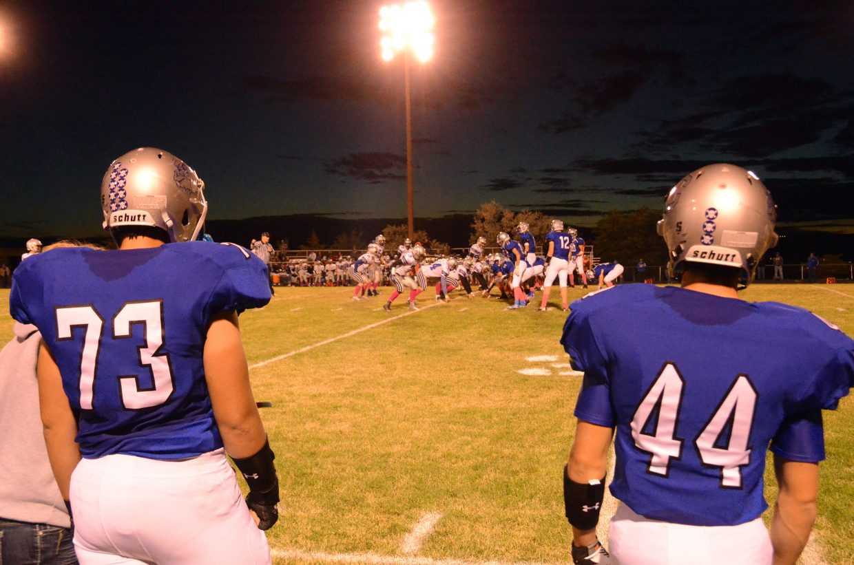 Moffat County High School senior Cory Summers, left, and sophomore Eddie Smercina catch their breath on the sidelines during the Bulldogs' Friday game against Coal Ridge. The team won, 34-0.