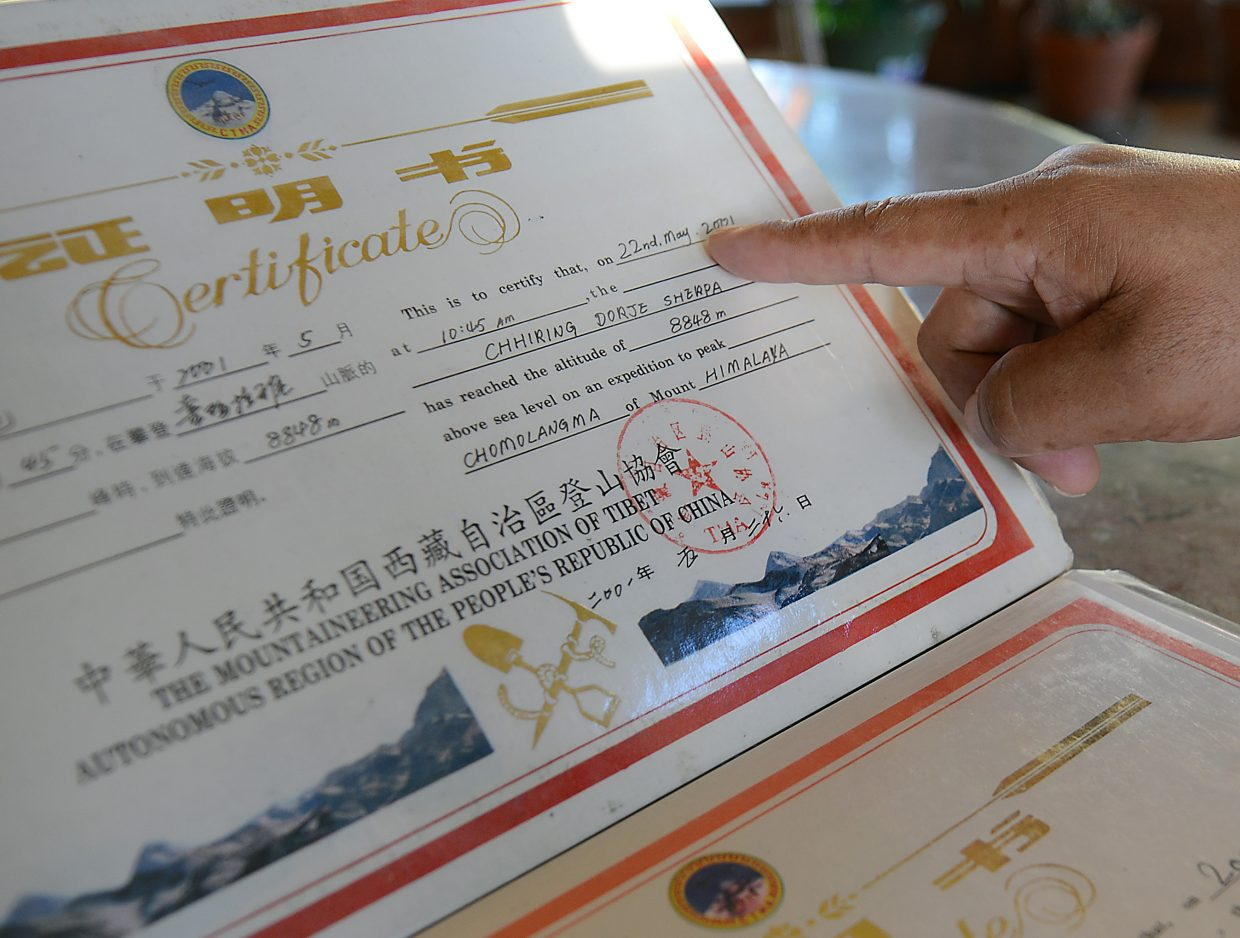 Chhiring Dorje Sherpa looks through certificates he's received for climbing 8,000-meter peaks.
