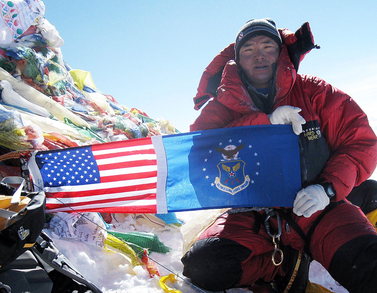Chhiring Dorje Sherpa holds up flags at the top of Mount Everest.