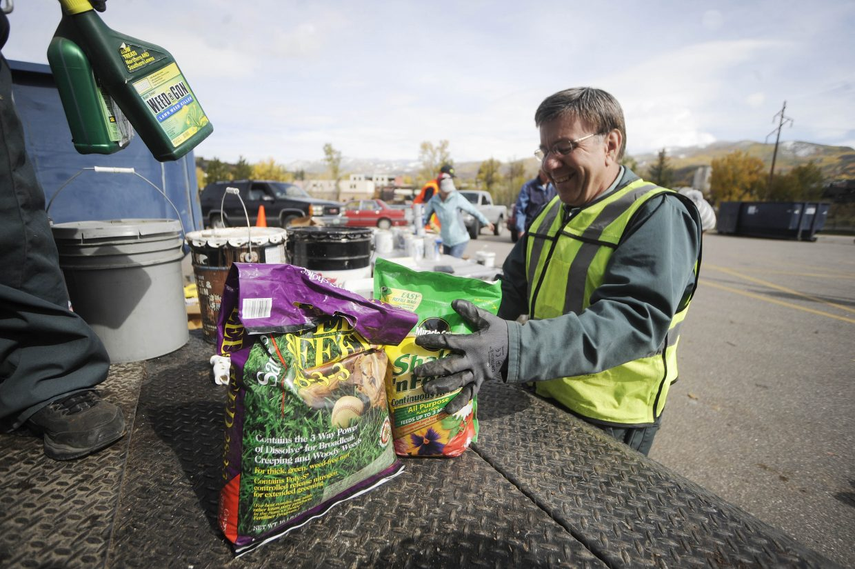 Len Cichon, with Waste Management, loads garden chemicals onto a truck during the Community Recycling Drop-Off Day on Saturday at Howelsen Hill.