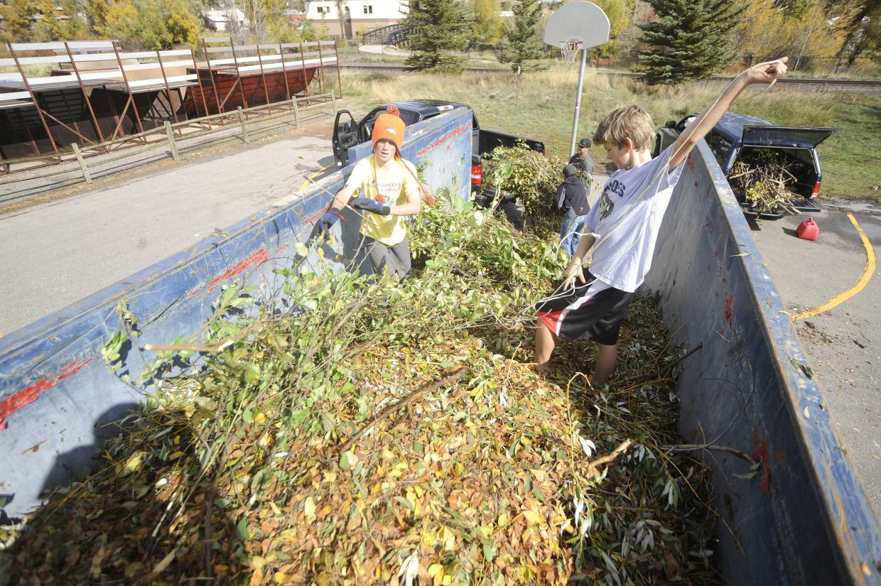 Lowen Epstein, left, and Ben Hoefer load yard waste into a container during the Community Recycling Drop-Off Day on Saturday at Howelsen Hill.