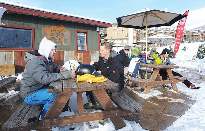 Tim Scalo and Michael Ricker enjoy a mild December 2014 afternoon on the deck of the T Bar. The owner of the bar at the base of Steamboat Ski Area is seeking to renew a city permit that would allow it to continue to operate in its temporary building for up to five more years.
