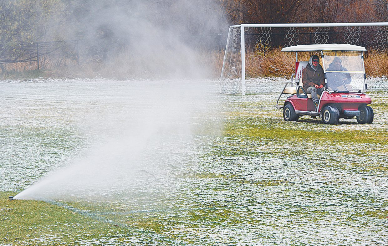 """Crews from the city of Steamboat Springs check on sprinkler heads while """"blowing out"""" the irrigation system at Emerald Park Wednesday morning. Crews use an air compressor to blow the remaining water out of the lines so that the pipes and heads don't freeze and crack in the winter months."""