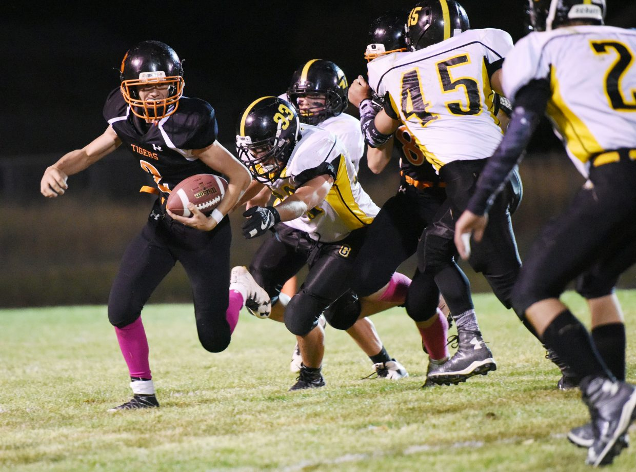 Hayden quarterback Garrett St. Clair rushes toward a pack of Gilpin County defenders Friday. The Tigers moved the ball at times but couldn't get into the end zone on one end of the field and couldn't stop Gilpin's big plays on the other. The Tigers lost 36-0.