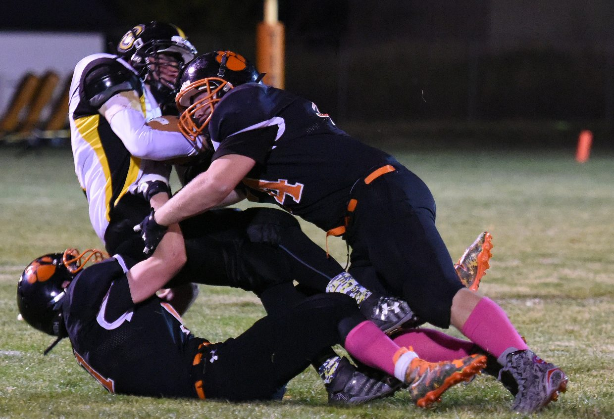 Hayden's Tyler Boyer, bottom, and Christian Carson team up to tackle Gilpin County's Alex Wilhelm on Friday.