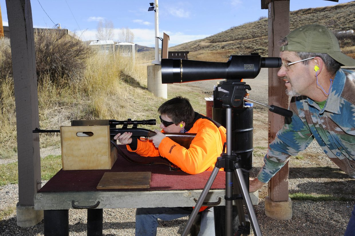 Jim Ficke watches his son Eric shoot Friday at the Routt County Rifle Club west of Steamboat Springs. The range was busy with hunters, who were getting ready for the rifle season, which starts Saturday. The rifle club allows guests to use the range for $5.