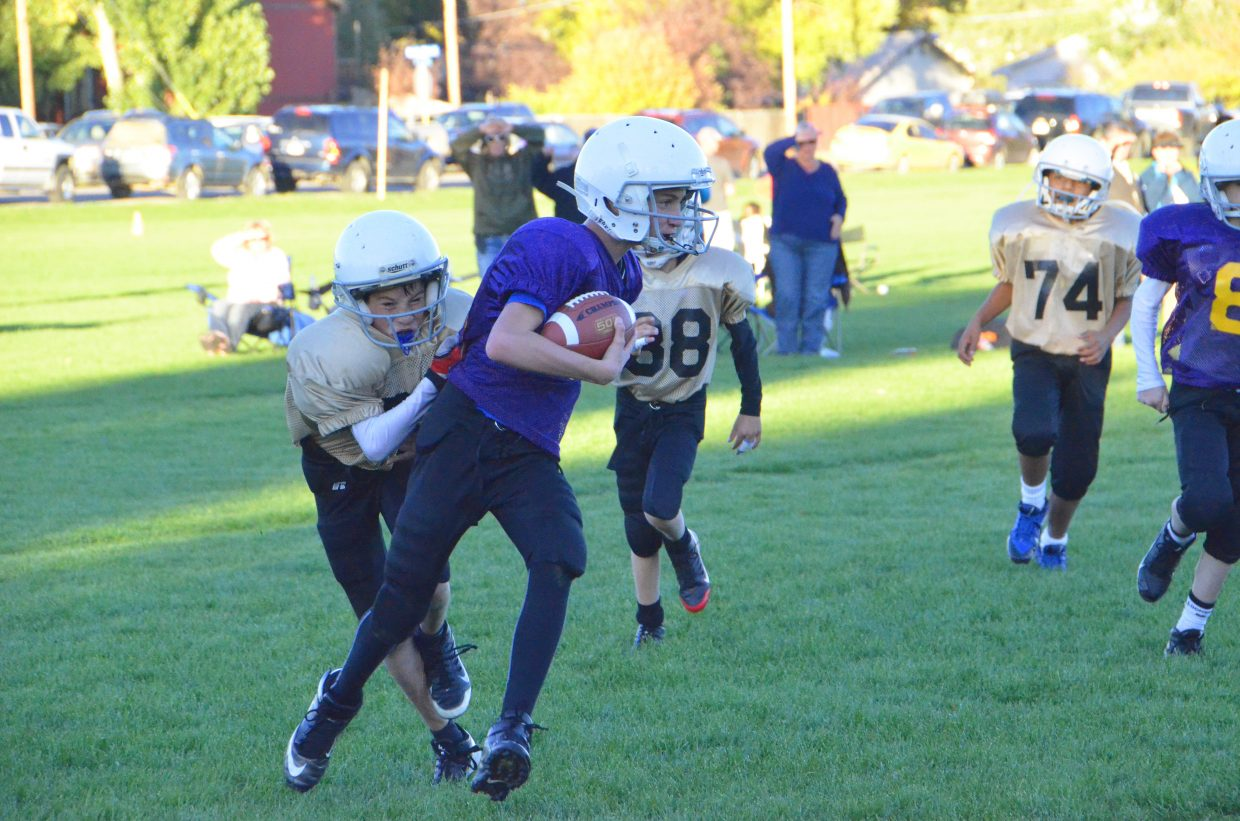 Tanner Etzler, of the Boy-Ko Supply Saints, wraps around Sean Byers, of the Craig Daily Press Vikings, Tuesday at Woodbury Sports Complex. The Vikings won, 26-13, for fifth place in the fifth- and sixth-grade division of Doak Walker tackle football.