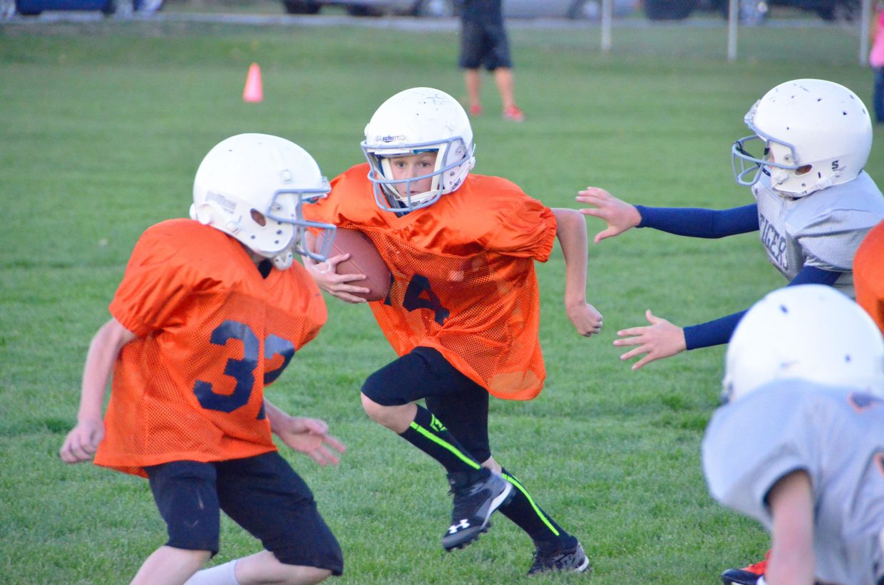 Donnie Quick, front, blocks for rusher Carter Behrman during the Cook Chevrolet Broncos' Tuesday game at Woodbury Sports Complex. The Broncos placed second in the fifth- and sixth-grade division of Doak Walker tackle football after a loss to the Hayden Tigers for the championship.