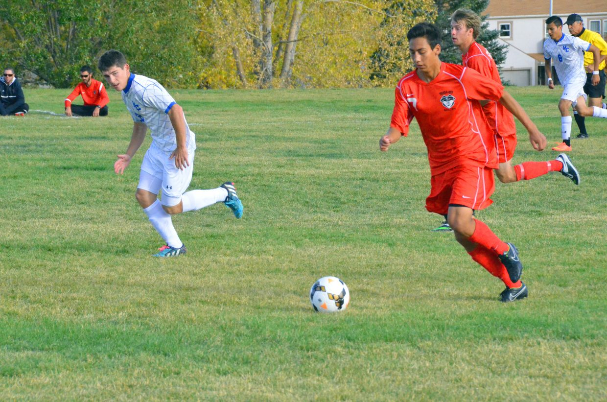 Steamboat Springs High School's Hector Lopez starts the move downfield while Moffat County High School's Hugh Turner switches to defense during the Bulldogs' varsity soccer game against the Sailors Thursday in Craig.
