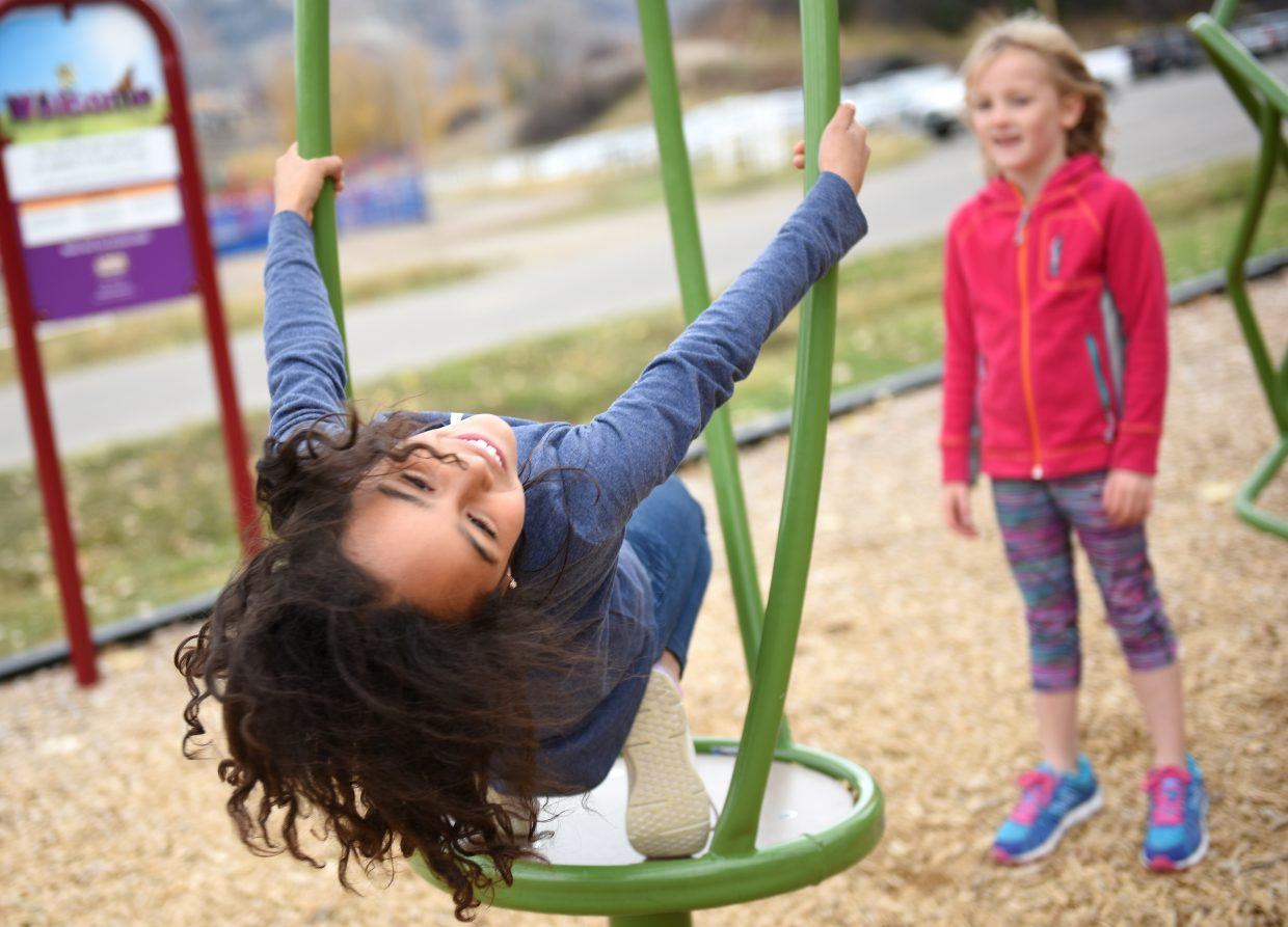 Lean into it: Bella Velez, 8, spins at the playground jungle gym at Howelsen Hill on Sunday, while Ella Jacobson, 6, waits her turn. The children were visiting Steamboat Springs with family from the Front Range.